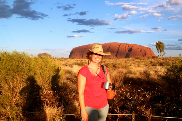 Drinking sparkling wine out of a tin cup at sunset by Uluru